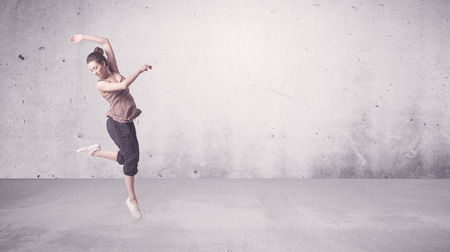 A beautiful young hip hop dancer dancing contemporary urban street dance in empty clear grey wall background concept. Reklamní fotografie - 53474084