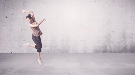 danza contemporanea: Una joven hermosa bailarina de hip hop bailando la danza contemporánea calle urbana en vacío clara pared gris del concepto del fondo.
