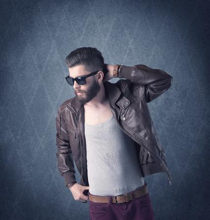 Un modelo de manera hermoso con la barba que se coloca delante del fondo de fantasía y haciendo muecas mientras se utiliza un concepto de cámara de la vendimia