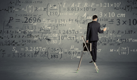 exponential: A businessman in elegant suit standing on a small ladder and writing numbers, calculating on grey wall background