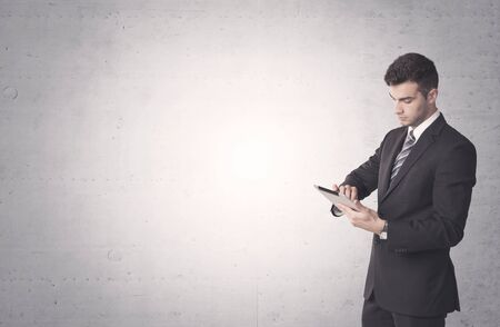business phone: Young sales business person in elegant suit standing in front of clear empty grey wall background while talking on the phone