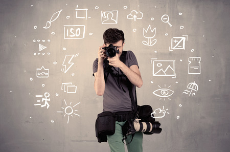 amateur: An amateur hobby photographer learning to use a professional digital camera with camera settings icons on the background wall concept
