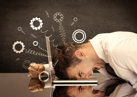 are fed: Falling apart illustration concept with cranks, cog wheels springing from a fed up and tired businessmans head resting on laptop keyboard Stock Photo