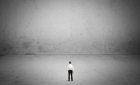 concrete background: A tiny elegant businessman standing in large empty urban space with concrete walls and grey background concept