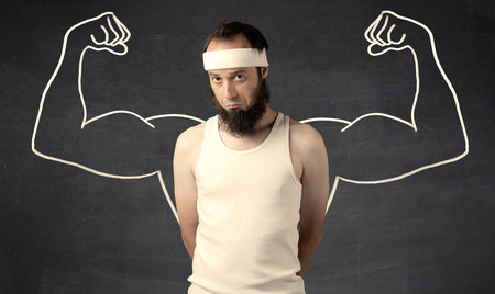 skinny: A young male with beard and glasses posing in front of grey background, thinking about lifting weight with big muscles, illustrated by white drawing concept. Stock Photo