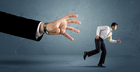 time to work: Business man running away from a huge hand concept on background