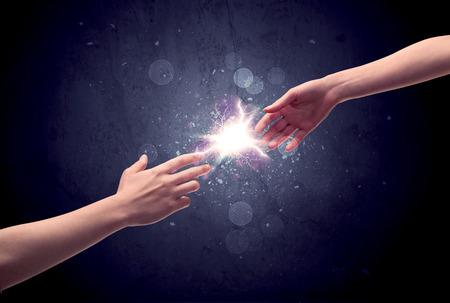 Dos manos masculinas alcanzando uno hacia el otro, casi tocando con los dedos, la chispa de iluminación en concepto de fondo de la galaxia