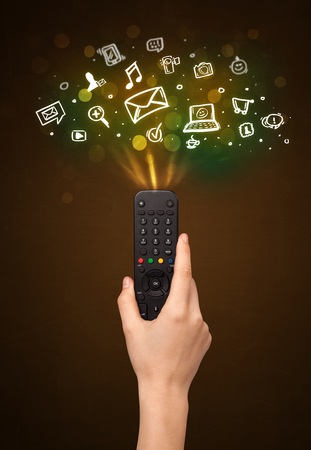 out of control: Hand holding a remote control, social media icons coming out of it