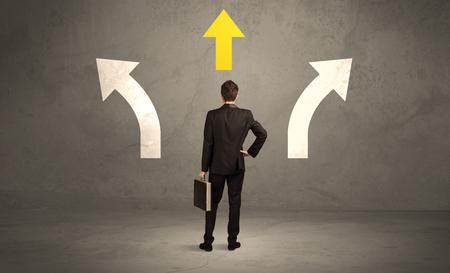 persona confundida: Un hombre de negocios confuso frente a una pared urbana gris con una flecha que apunta en la direcci�n amarilla concepto correcto