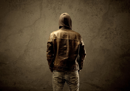 Un sospechoso de sexo masculino maduro sin rostro en el ambiente urbano oscuro y claro en frente de un fondo de hormigón pared vacía Foto de archivo