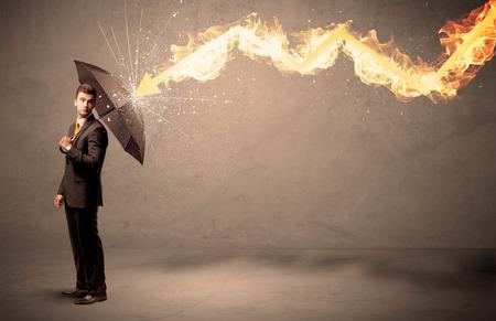 Biznes człowiek broniąc się ze strzałką pożarnej z parasolem na tle grungy