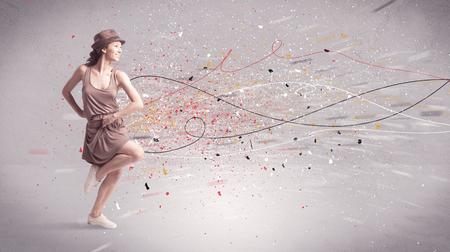 Ein junger zeitgenössischer energetische Tänzer in der Tätigkeit vor einem grauen Wand Hintergrund mit Linien, Spray Punkte und Splatter-Konzept