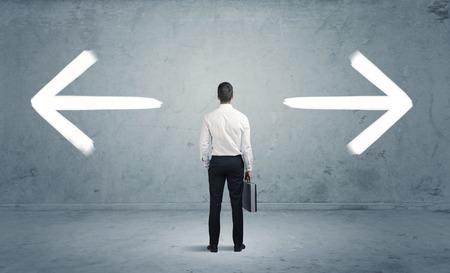flecha direccion: Un hombre de negocios de duda, tener que shoose entre dos opciones diferentes indicadas por las flechas que apuntan en dirección opuesta concepto Foto de archivo