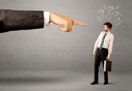 jefe enojado: Aficionado joven confundido empresario no entender por qué se está concepto disparó con signos de interrogación dibujado y gran jefe mano que señala a él Foto de archivo