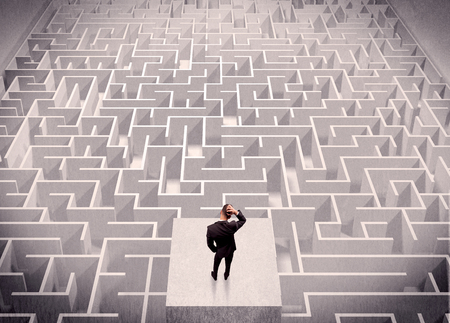 wayout: A confused businessman thinking while standing on a square platform above a detailed maze