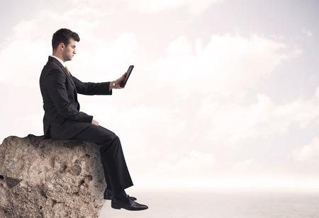 sales person: A young sales person in elegant suit sitting with paper on top of a stone in the clouds concept