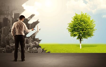 transforming: Businessman in elegant suit standing with his back, holding a roller and transforming the grey city landscape into green tree in bright nature environment concept