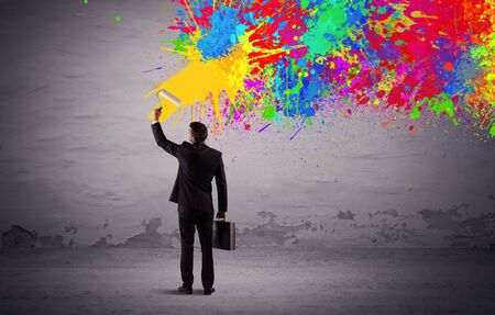 transforming: An elegant businessman in suit painting colorful splatter, bright colors on grey urban wall with a paint roller in his hand concept Stock Photo