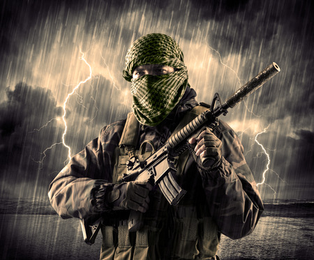 attacker: Portrait of a dangerous armed terrorist with mask and gun in a thunderstorm with lightning