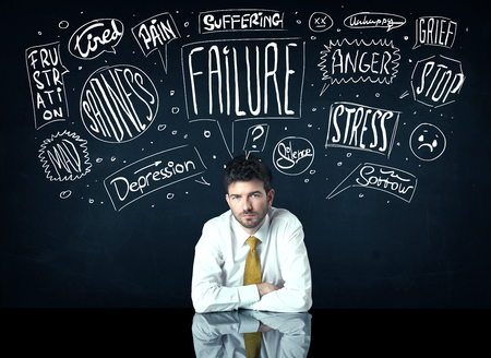 indecisive: Young depressed businessman sitting under white drawn trouble thought boxes Stock Photo