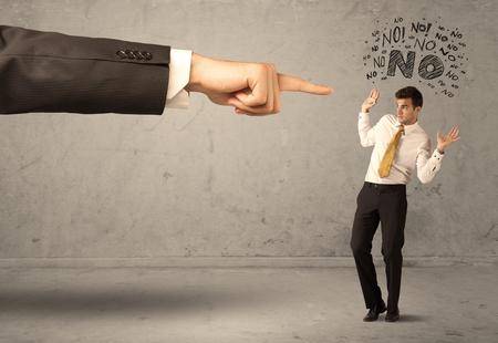désolé: Un jeune employé désaccord et discuter avec le patron, se sentant notion honte. Une grande main pointant affaires de dire non Banque d'images