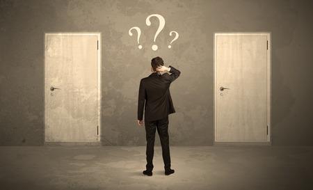 dois: Vendedor de pé na frente de duas portas, incapaz de fazer o conceito decisão certa com pontos de interrogação sobre sua cabeça