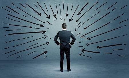 confundido: Un hombre de negocios confusa bajo pressur despu�s de hacer una mala decisi�n ilustrada ahora con flechas apuntando a �l en claro concepto espacio urbano azul Foto de archivo