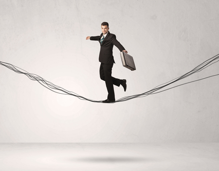A confident businessman with briefcase walking forward on drawn lines, cables in empty grey  space concept Stock Photo