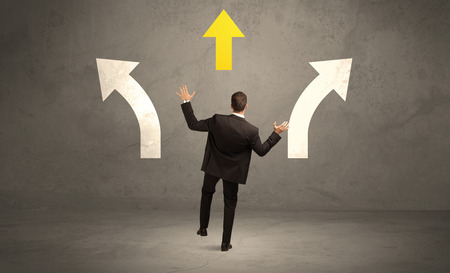 considerations: A confused businessman facing a grey urban wall with a yellow arrow pointing in the right direction concept