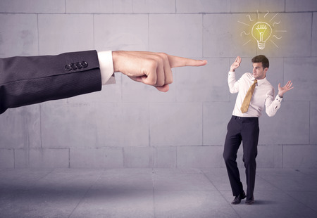 A huge ordering hand pointing at scared and confused businessman with a good idea illustrated by a drawn glowing light bulb concept Stock Photo