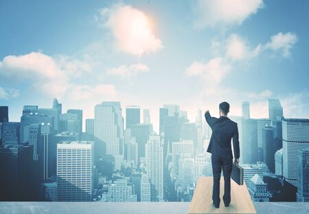 people looking: Businessman standing on a roof and looking at future city Stock Photo