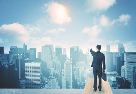 Empresario de pie sobre un techo y mirando a futuro de la ciudad
