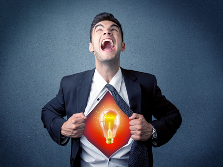 inteligent: Businessman ripping off shirt and idea light bulb appears on his chest concept on backround