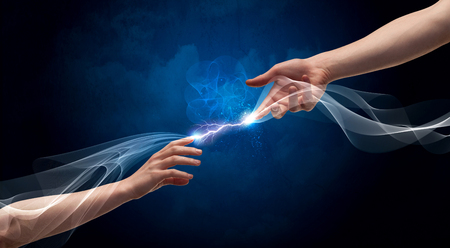 current: Two male arms reaching for each other, with a smoking electric current connecting their fingers in empty space background concept Stock Photo