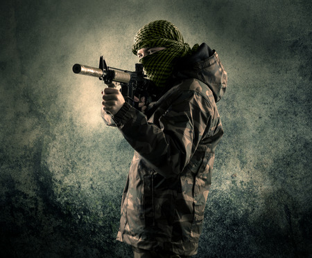 against the war: Portrait of a heavily armed masked soldier with grungy background concept