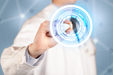cross ties: A male  doctor in white coat showing a glowing pill in blue, white circles Stock Photo