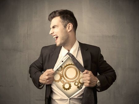 team ideas: Businessman tearing shirt off and machine cog wheel shows on his chest concept on background Stock Photo