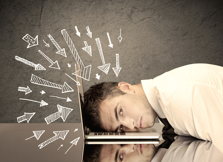banging: An exhausted business person resting his head on keyboard with pressure illustrated by arrows pointing at him concept Stock Photo
