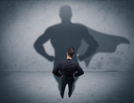 Un fiducioso giovane venditore elegante con la valigetta di fronte a un muro, guardando il suo concetto ombra superman Archivio Fotografico