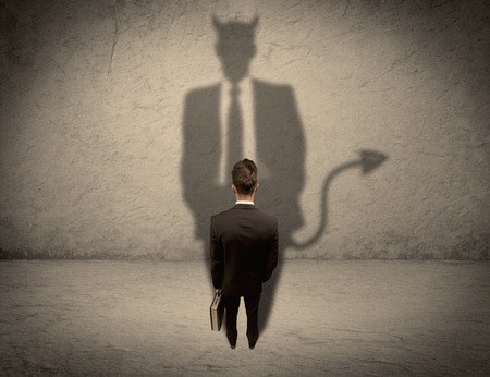 people shadow: An experienced tricky businessman in suit looking at his devil desguise shadow reflected on the wall concept