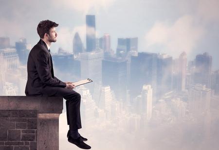 Un joven hombre de negocios sentado en el borde de un edificio en frente de un fondo centro de la ciudad scape con edificios altos y cielo concepto