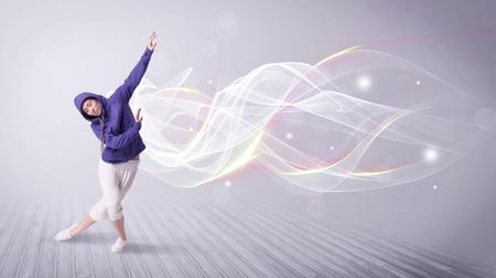 Una joven hermosa bailarina de hip hop bailando la danza contemporánea urbana de la calle en frente de la pared de fondo gris con líneas smokey y el concepto de brillo.