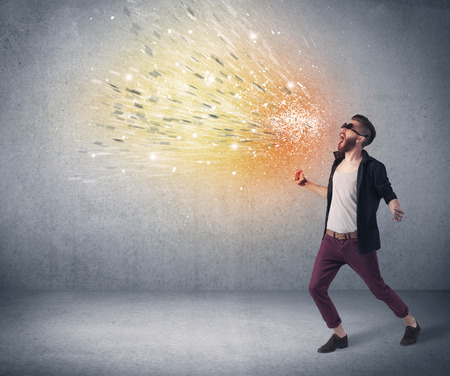 A young hipster guy with beard and sunglasses shouting in front of urban wall with vomit like colorful paint splatter on wall concept Stock Photo