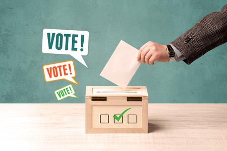 voting: A hand placing a voting slip into a ballot box Stock Photo