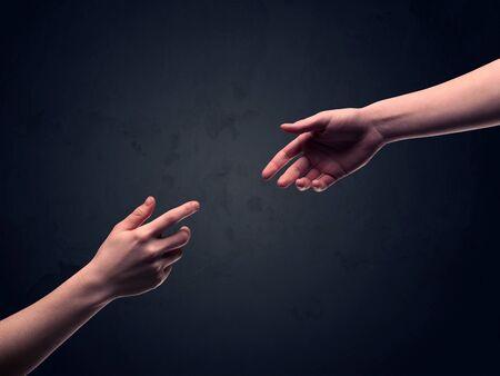 Due mani maschili raggiungere gli uni agli altri, quasi commovente, di fronte a chiaro sfondo vuoto concetto di muro scuro