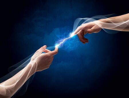 other space: Two male arms reaching for each other, with a smoking electric current connecting their fingers in empty space background concept Stock Photo