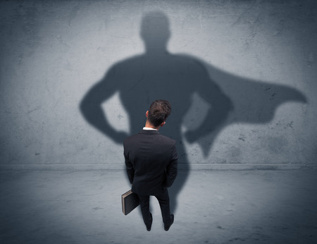 facing a wall: A confident young elegant salesman with briefcase facing a wall, looking at his super hero shadow concept Stock Photo