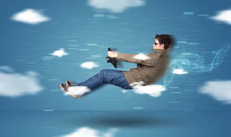 Racedriver divertido joven de conducción entre nubes concepto sobre fondo azul Foto de archivo
