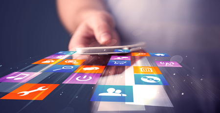 application icons: Man holding smart phone with colorful application icons comming out