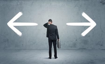 Een zakenman in twijfel te moeten shoose tussen twee verschillende keuzes aangegeven met pijlen in tegenovergestelde richting begrip